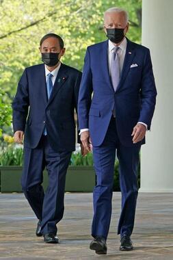 バイデン大統領とスーツ姿でホワイトハウスを歩く菅首相(写真:AFP/アフロ)