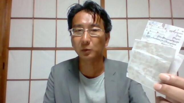 ミャンマーから記憶したフリージャーナリストの北角裕樹さん。拘束中はペンが使えず、コーヒーを使って書いたメモをカメラに向かって示した(写真は日本外国特派員協会の配信動画から)