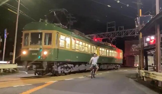 江ノ電と並走しながら左手を上げる自転車の男性(「ネイマール東日本」さん(@Gifu_Hashima)投稿の動画から)