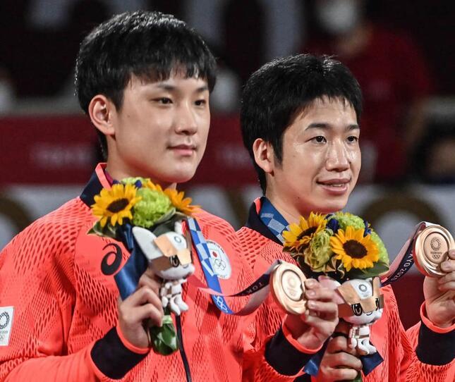 張本選手(左)と水谷選手(写真:AFP/アフロ)