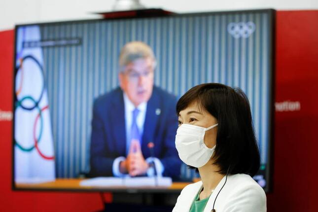 丸川珠代五輪担当相と、スクリーンに映るトーマス・バッハIOC会長(写真:代表撮影/ロイター/アフロ)