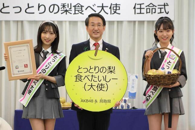 新曲が縁でAKB48が「とっとりの梨食べ大使」に任命され、任命式が開かれた。左からAKB48の小栗有以さん、鳥取県の平井伸治知事、AKB48の山内瑞葵さん