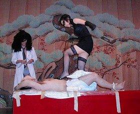 「女王様」役の女性が、おむつ着用の患者役の男性を踏みつけている