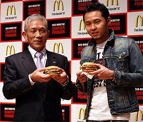 「クォーターパウンダー」を手にする原田泳幸社長(左)と北島康介選手(右)