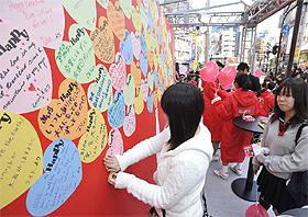 壁一面埋め尽くされた「Happy Message」。伝えたい想いを書き込んだあとは、嬉しそうな笑顔をのぞかせていた