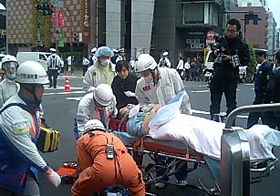救急隊員によって搬送される負傷者