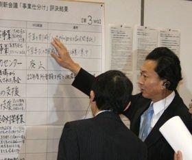 事業仕分けの結果が書き込まれたボードに見入る鳩山由紀夫首相