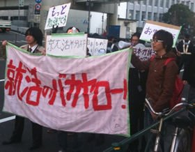 「就活のバカヤロー!」と書かれた横断幕をもって東京・日本橋付近を歩く大学生たち