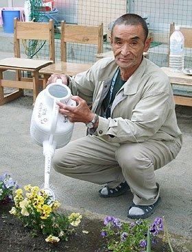 花が趣味の三浦さん。避難所の花壇の水やりが日課になっている=大槌町の安渡小学校避難所で