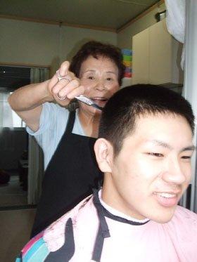 孫の頭を刈る越田さん。自然と顔がほころぶ=大槌町の第7仮設住宅の玄関先で