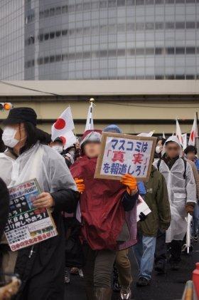 プラカードを手に行進するデモ隊。後方に見えるのは電通本社ビル