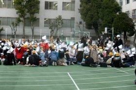グラウンドで防空ずきんをかぶって保護者を待つ生徒たち