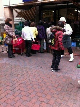 スーパーに並ぶ人々。