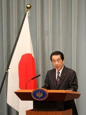 国旗を背に会見に臨む菅首相。国旗からは喪章が取り外されていた