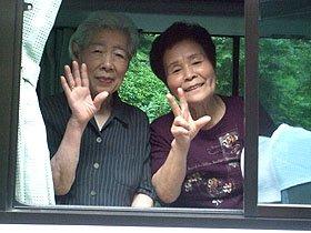 手を振って別れを告げる倉沢さん(左)と越田さん=大沢温泉自炊部で