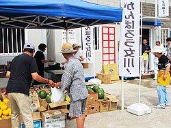 果物が次々売れていきます。この商店街の会長を務める青果店の相原さん(左)は、元のお店が津波ですっかり流されてしまったそうです(7月1日、女川町)