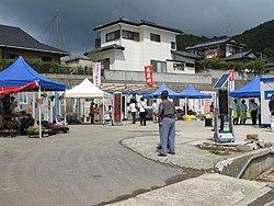 おながわコンテナ村商店街。コンテナハウスの青いラインに合わせた、白と青のテントがおしゃれです(7月1日、女川町)