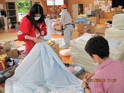避難所となっている小学校で、新しく配付した布団にシーツをかぶせる難民を助ける会の関井瑞穂(左)