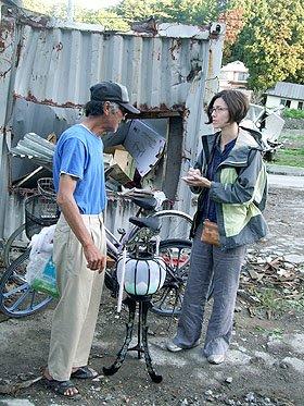 瓦礫を背に被災者から話を聞くアレッシアさん=大槌町安渡地区で