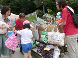 好きな柄のトートバッグを選ぶ子どもたち。右は難民を助ける会の高橋智美