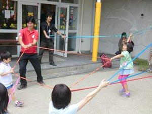 色とりどりのゴムバンドを使って遊ぶ子どもたち。左奥は難民を助ける会の小菅健太郎