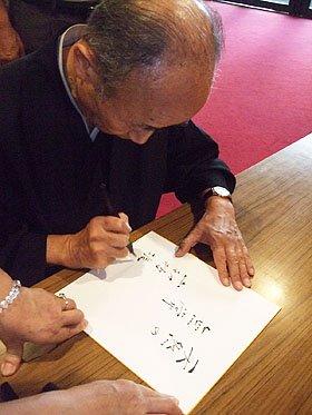 色紙を求められた山折さんは「天然の無常」と書いた=花巻市文化会館で