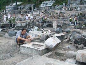 倒れた墓石の上で迎え火をたくお年寄り=大槌町の江岸寺で