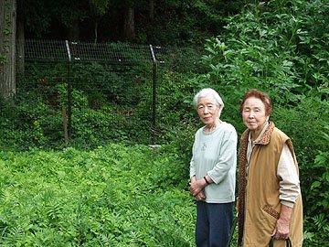 山際に設置されたクマ侵入防止用の柵の前に立つ倉沢さん(左)と岩崎さん=第9仮設住宅で