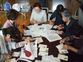 絵葉書づくりに精を出す被災者の人たち=花巻市南万丁目の自治会館で