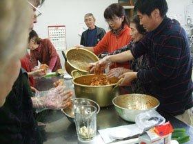 熱心にキムチ作りを学ぶ被災者のみなさん。右端が尹さん=花巻市の南万丁目自治会館で