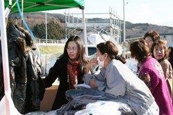 冬物衣類などを無料提供するテントには、仮設住宅の方々による長い行列が。左は商品について説明されるイオン・スカラシップ奨学生の冉剣玲さん(左)