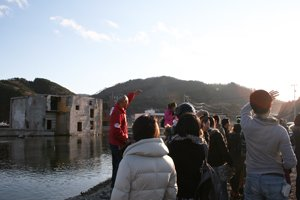未だに瓦礫の残る被災地で、震災当日の津波の高さを指し示す難民を助ける会の大松修司(左)