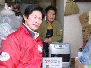 宮城県松島町の高田さん。海沿いにあったご自宅には津波が押し寄せ、今は更地だといいます。「寒くなってきたのにエアコンの調子が悪く、ファンヒーターは助かります。」(2011年12月22日、左は難民を助ける会仙台事務所の小菅健太郎)