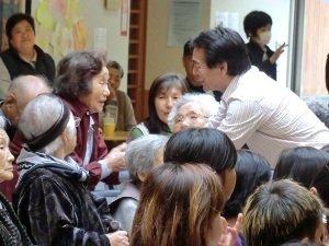 「ずっと大ファンだったんです!」と江戸家猫八さん(右)の手を<br />固く握りしめる被災者の女性(宮城県石巻市 2011年4月27日)