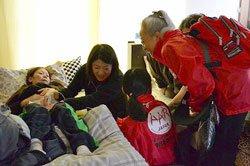 4カ月の妊婦さんを訪問し診察する貫戸医師(中央)。赤ちゃんの映像に歓声が上がる(宮城県石巻市 2011年4月30日)