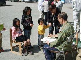 似顔絵を描いてもらう子どもたち=大槌町安渡小学校で