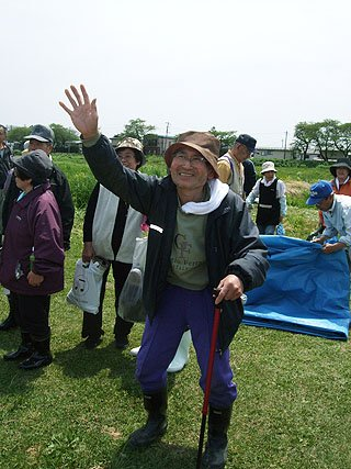 園児たちの激励に手を振って感謝する被災者の老人