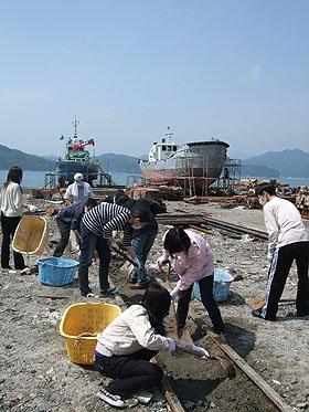 土砂の撤去に汗を流す留学生ら=大槌港で