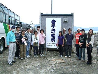 再建を目指す岩手造船所の看板の前で記念撮影=大槌港で