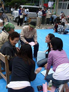 「悲しみを分かち合い、これからも支え合っていこう」と語り合う被災者と留学生たち=安渡小学校の避難所で
