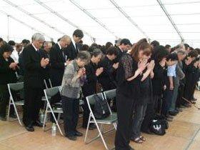手を合わせ、犠牲者の霊に黙とうする遺族たち