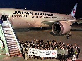 成田空港に到着したJALのボーイング787型機。社員が横断幕で迎えた