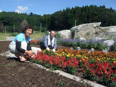 「道慶翁碑」がある石碑の前で花の手入れをする紺野さん(左)と熊谷さん=陸前高田市高田町森の前で