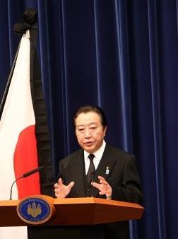 弔旗を背に会見する野田佳彦首相