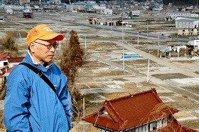 高台から鹿折地区を見つめる佐々木さん。背後には津波で流されてきた大型船も見える