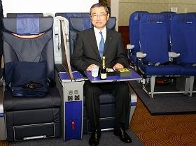 新型プレミアムシートに腰掛ける伊東信一郎社長。テーブル上は新機内食「プレミアム御膳」。右奥は新普通席シート