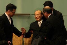 周囲に体を支えられる杉田和博官房副長官(71)。この後、SPによって運び出された