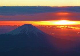 高度5200メートルから眺める初日の出と初富士。搭乗客は熱心にカメラに収めていた