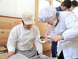 パン製造販売担当の障子上喜一さん(左)に教えてもらってジャムパンを作ります(2012年1月31日)