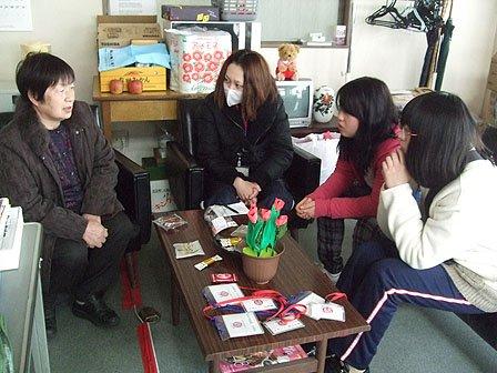 泉田さん(左)の体験談に聞き入る学生たち=花巻市内の「ゆいっこ花巻」の事務所で